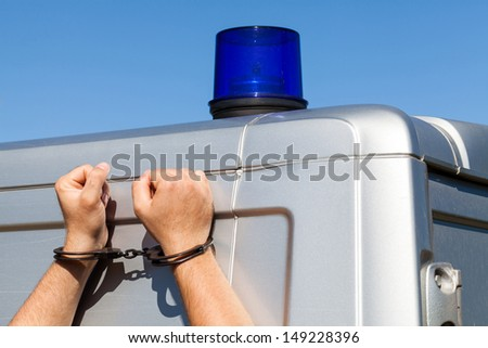 arrested a criminal rests her hands in handcuffs by police car - stock photo