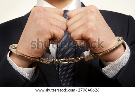 Arrested business man handcuffed hands. Close-up.   - stock photo