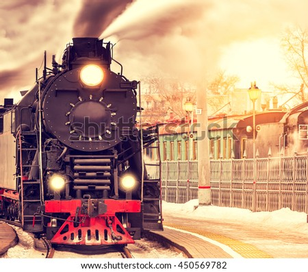 Arrival of the retro steam train at sunset time. - stock photo