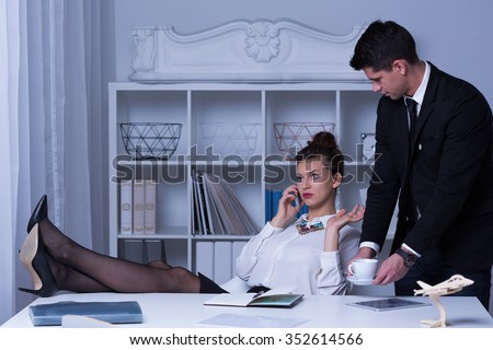 Arrogant business woman with legs on the desk - stock photo
