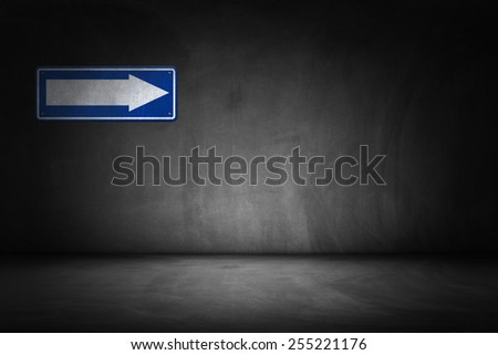 Arrow directional sign on dark black wall - stock photo