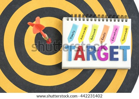 Arrow in bullseye with alphabet letters words target on the notebook with handwriting timely achievable relevant goals education teamwork over dartboard background - stock photo