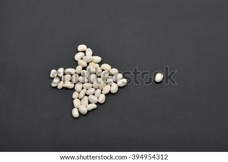 Arrow made from white beans, pointing the way by a bean on black background. Food vegan, vegetarian. Healthy food - stock photo