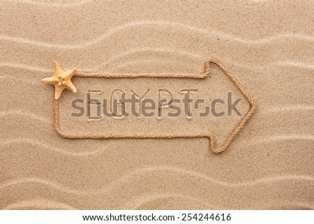 Arrow made of rope and sea shells with the word Egypt  on the sand, as background - stock photo