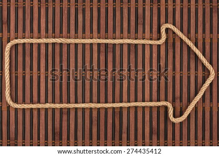 Arrow made of rope  lies on a bamboo mat, can be used as background, texture - stock photo