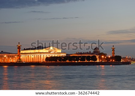 Arrow of Vasilevsky island, Rostral columns and Naval Museum illuminated at sunset, the reflection in the water of the river Neva in St. Petersburg summer night