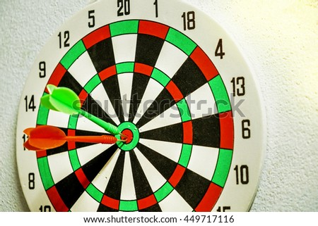 Arrow red and green dart hitting the target in the center of the dart. - stock photo