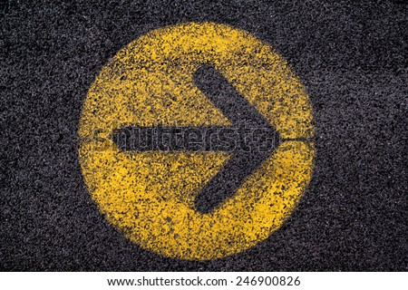 arrow sign in yellow circle painted on black asphalt - stock photo