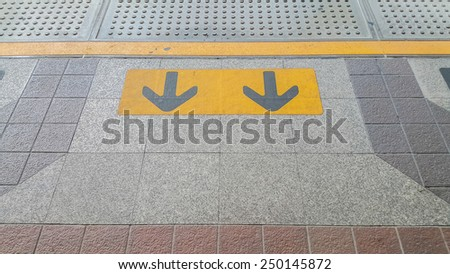 arrow sign in yellow color painted on black on the waiting zone for train, subway - stock photo