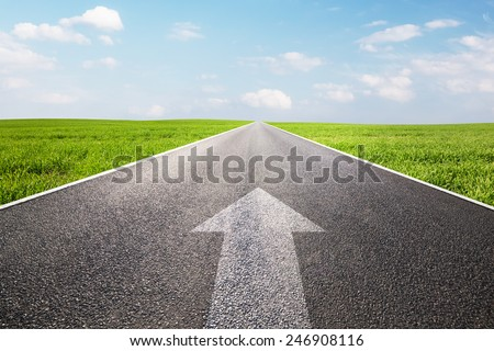 Arrow sign pointing forward on long empty straight road, highway. Conceptual - travel, goal, future perspective etc. - stock photo