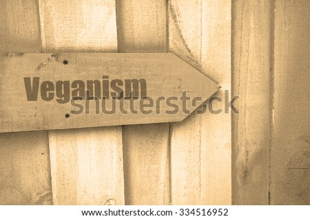 arrow sign with the word veganism on wood - stock photo