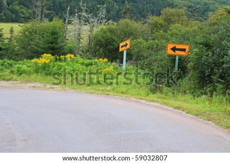 Arrow signs pointing both ways on a steep curve in New Brunswick, Canada - stock photo