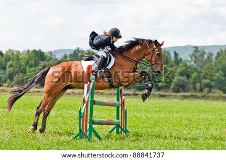 "ARSENEV, RUSSIA - SEPTEMBER 03: Unidentified child-rider in action jumps over a hurdle at horse on the show jumps ""Cup of Governor of the Primorsky Territory, 2011"" on Sept 03, 2011 in Arsenev, Russia - stock photo"