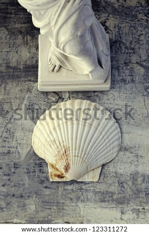 Art and beauty natural still life of goddess statue's feet and scallop seashell. - stock photo