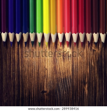 Art background. Color pencils on wood background. Retro stale. - stock photo