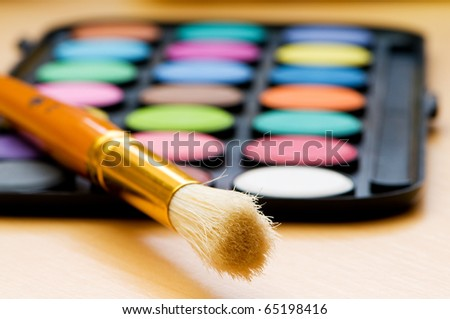 Art concept with painters palette and paint brush - stock photo