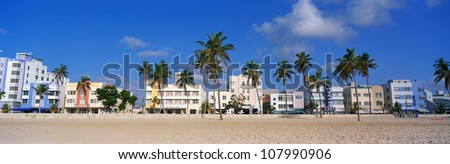 Art deco district of South Beach Miami. The buildings are painted in pastel colors surrounded by tropical palm trees. - stock photo