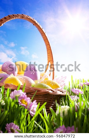 art Easter basket with Easter eggs on spring lawn - stock photo