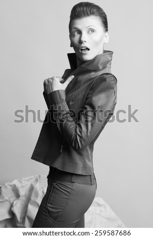 Art fashion concept. Portrait of androgynous model with short hair posing over gray background. Pale skin, wow face, natural make-up. Close up. David Bowie style. Studio shot - stock photo