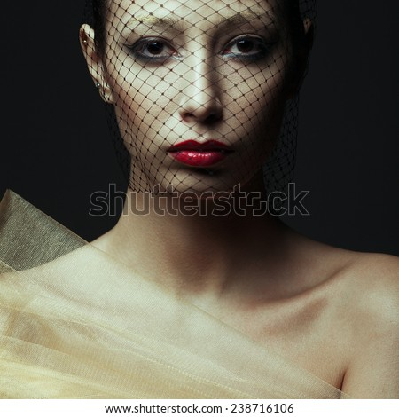 Art fashion concept. Portrait of sensual beautiful brunette looking at camera through black veil and posing over dark gray background. Golden eyebrows, red wet lips. Close up. Vogue style. Studio shot - stock photo