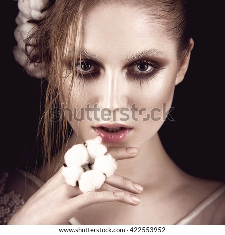 Art fashion girl with creative makeup and cotton. Beauty face.