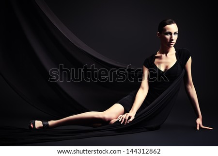 Art fashion photo of a beautiful woman in black dress. Over black background. - stock photo