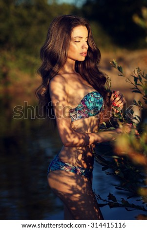 Art fashion portrait of young stunning pretty female model posing in blue bikini in forest lake at sunset. Soft warm evening lightning and beautiful shadows at girl body - stock photo