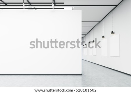 art gallery with large white wall and several empty banners hanging on white wall concrete