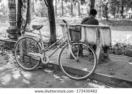 art lonely man and his bicycle at reversed. black and white. - stock photo