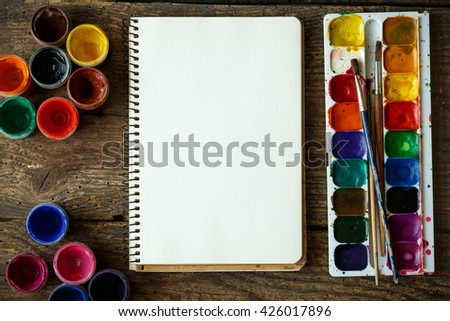 Art of Painting. Painting set: paper, brushes, paints, watercolor, acrylic paint on a wooden background top down view - stock photo