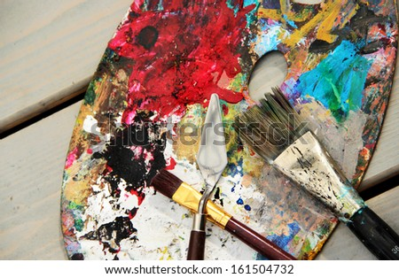 Art palette and brushes with a lot of vivid colors    - stock photo