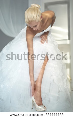 Art photo of a beautiful bride. Dressing shoes - stock photo