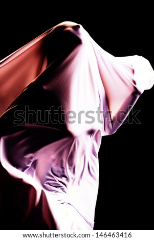 Art photo of a female silhouette breaking through the fabric. Struggle concept. - stock photo