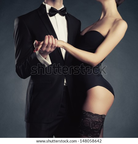 Art photo of a young couple in sensual lingerie and a tuxedo - stock photo