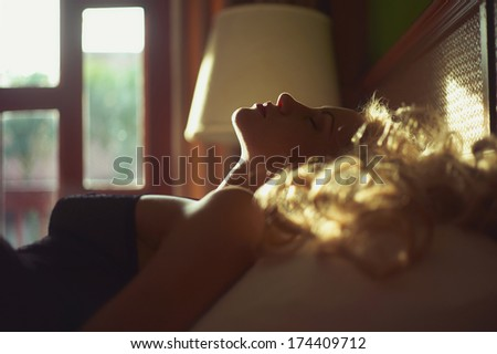 Art photo of beautiful blonde in bed in the sun - stock photo