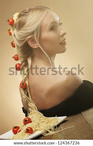 Art photo of young beautiful woman with pasta and tomatoes in her hair - stock photo