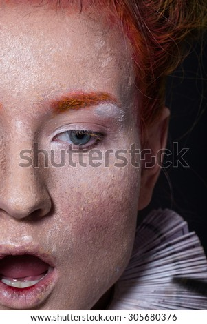 Art picture of a girl with creative make-up, textured leather, red-orange tones on a black background