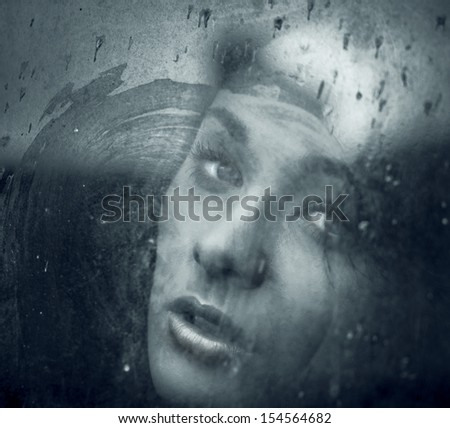 Art portrait of a beautiful young spooky woman, looks through grunge styled rainy window.  - stock photo