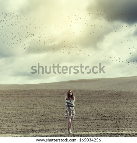 Art portrait of a lonely girl in a field - stock photo