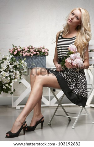 Art portrait of fashion model posing in the chair, holding a bunch of peonies