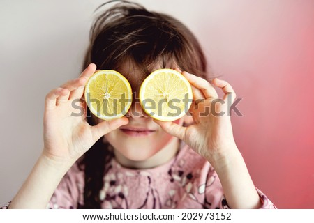 Art portrait of little girl with juice lemons as eyes: rose tone - stock photo