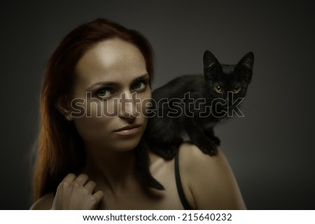 Art portrait of redhead young woman with black cat on shoulder. Shallow depth of field - stock photo
