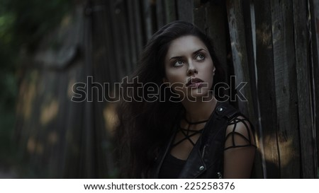 Art portrait of young gorgeous brunette outdoors. Shallow depth of field. Low key - stock photo