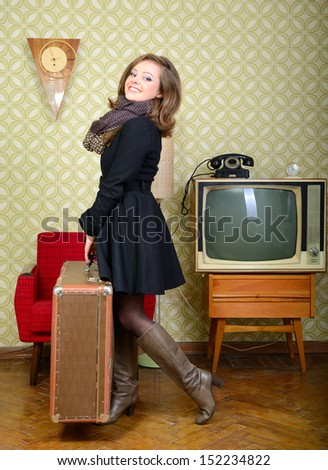 art portrait of young woman holding big suitcase in room with vintage wallpaper and interior with tv, clocks, chair and suitcase, retro stylization 60-70s, toned