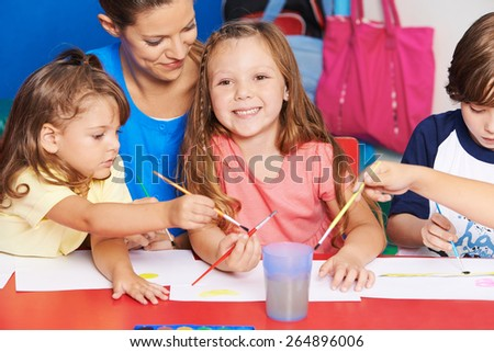 Art teacher and children painting images together in elementary school - stock photo