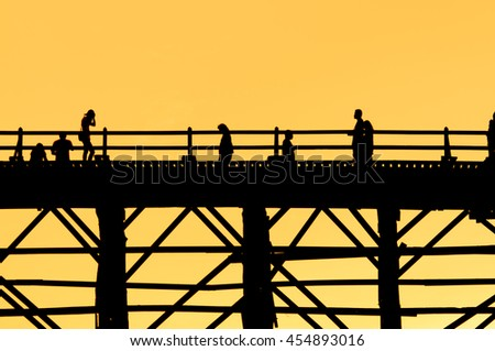 Art tone,Silhouette of People crossing on old wooden bridge(Mon Bridge) in Sangkhlaburi at sunset.Thailand