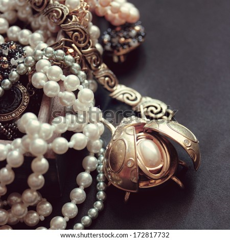 art vintage golden and pearl bijouterie with scarab  on black silk background in sepia and peach; square card  - stock photo