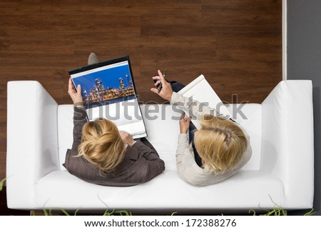 Artdirector critiquing an artist's portfolio, sitting leisurely on a couch in a modern office, seen from above - stock photo
