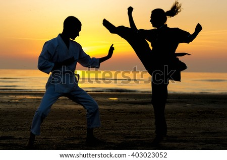 Artial marts fight between master and his pupil at the beach during the sunrise - silhouette - concept about people, lifestyle and sport - stock photo