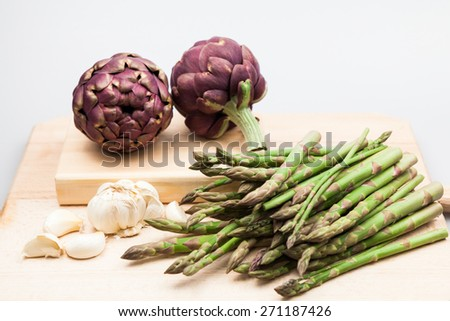 Artichokes, asparagus stems and garlic on a wooden kitchen board - stock photo